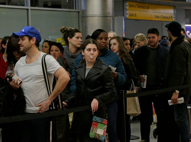 Travelers wait in line at a security checkpoint at La Guardia Airport in New York City, November 25, 2015