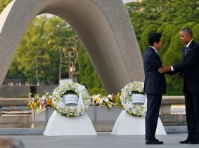 U.S. President Barack Obama puts his arm around Japanese Prime Minister Shinzo Abe after they laid wreaths in front of a cenotaph at Hiroshima Peace Memorial Park in Hiroshima, Japan, May 27, 2016