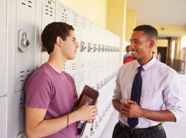 High school student talking to a teacher near lockers