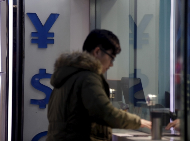 A man is seen next to signs of Chinese yuan and U.S. dollar at a foreign exchange store in Shanghai, January 8, 2016