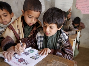 Boys study with a shared book at their school in a village outside Sanaa, Yemen, February 2, 2016