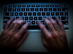 Hands on a keyboard in a dark room