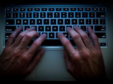 Hands on a keyboard in a dark room