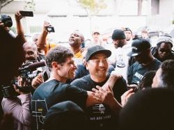 Chefs Daniel Patterson (left) and Roy Choi (center) celebrate during a ribbon-cutting ceremony at the restaurant Locol in the Watts neighborhood of Los Angeles, California