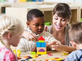 Children and their teacher building with colorful blocks