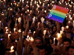 People take part in a candlelight memorial service the day after a mass shooting at Pulse, a gay nightclub in Orlando, Florida, June 13, 2016