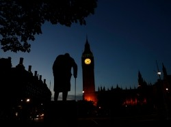 Dawn breaks behind the Houses of Parliament and the statue of Winston Churchill in Westminster, London, Britain, June 24, 2016