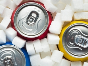 Cans of soda surrounded by sugar cubes, photo by piotr_malczyk/iStock
