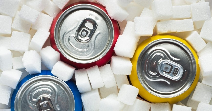 Cans of soda surrounded by sugar cubes