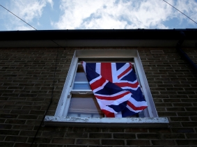 A British flag flutters in front of a window in London, Britain, June 24, 2016 after Britain voted to leave the European Union in the EU BREXIT referendum. Photo by Reinhard Krause/Reuters