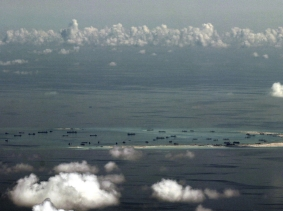 An aerial photo taken though a glass window of a Philippine military plane shows the alleged on-going land reclamation by China on Mischief reef in the Spratly Islands in the South China Sea, west of Palawan, Philippines, May 11, 2015.