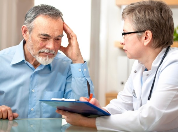 A man and his doctor discussing his treatment and looking at a clipboard