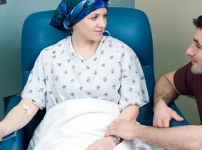 A patient receives chemotherapy while a loved one comforts her, photo by Mark Kostich/iStock