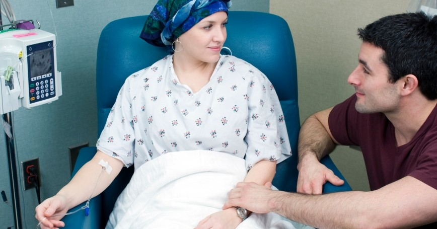 A patient receives chemotherapy while a loved one comforts her