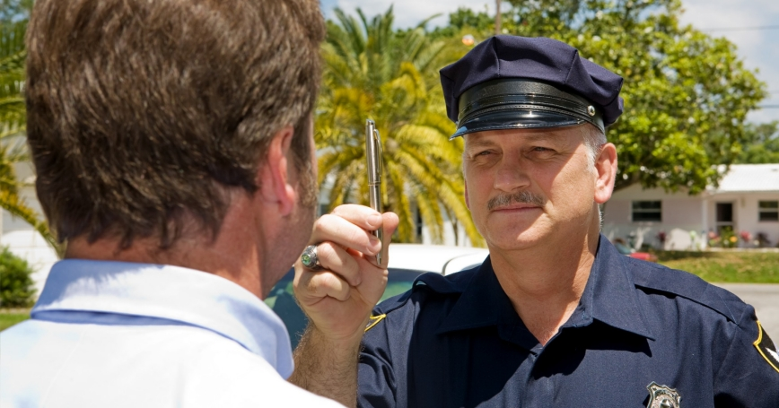 A police officer holds a pen and conducts a field sobriety test on a motorist