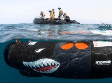 Aerographer's mates stand by as an unmanned underwater vehicle leaves the surface to search for mines as part of a training exercise