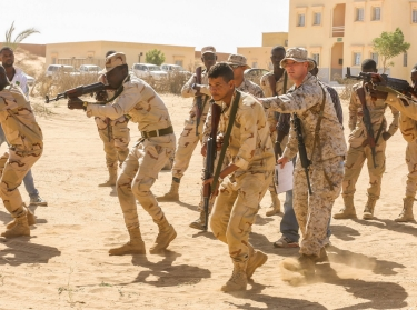 Staff Sgt. Todd Reinert, a motor transportation operations chief, guides soldiers through shooting drills prior to a live-fire range in Tiguet, Mauritania, Feb. 15, 2016.
