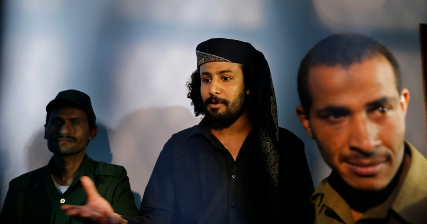 Sami Dayan (center), an al Qaeda militant, is escorted by police in a courtroom holding cell in Sanaa, Yemen, April 22, 2014