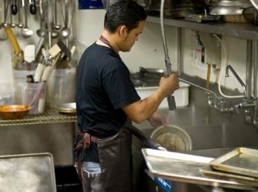 A dishwasher working in a restaurant kitchen