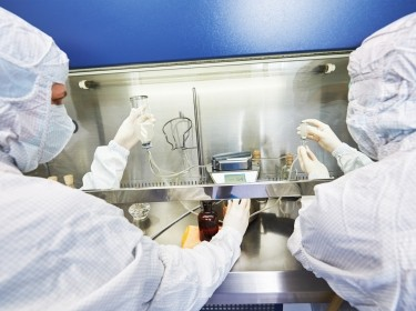 Two scientists in protective gear working in a microbiology laboratory