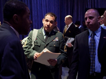 Sergeant First Class Steven Davila listens to a spokesperson for the Department of Veteran Affairs at a job fair in New York City, March 28, 2012