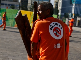 """A worker wears a sign that reads """"Shoo Zika!"""" in Portuguese on his back in Olympic Park in Rio de Janeiro, Brazil, July 31, 2016"""