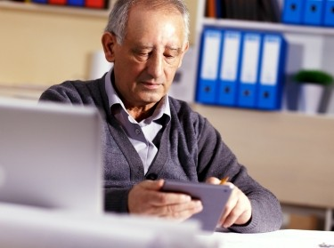 A senior man working on a tablet