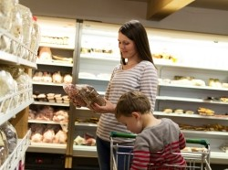 A women compares food labels in a grocery store while her child fidgets in the cart