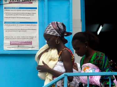 Women walk near a poster displaying a government message against Ebola, at a maternity hospital in Abidjan, Ivory Coast, August 14, 2014