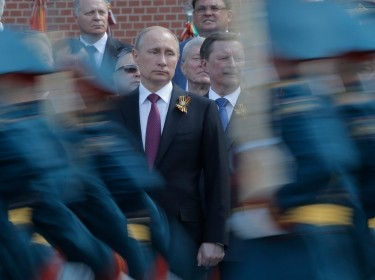 Russian President Vladimir Putin watches honor guards during a wreath-laying ceremony near the Kremlin in Moscow, May 9, 2016
