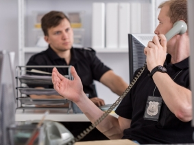 A police officer talking on the phone at his desk