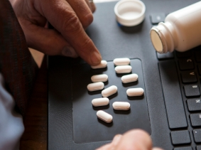 A man counting pills on his laptop