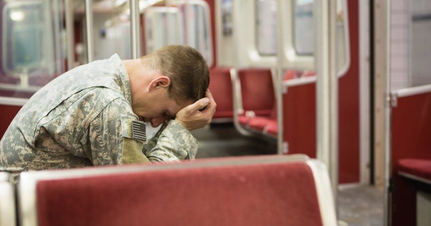 Soldier on a train resting his head in his hands