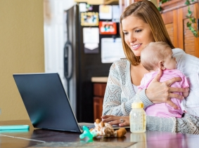 Mother holding her baby while working from home