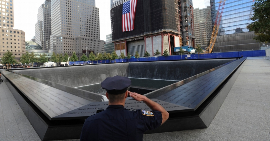 New York City Police Officer Danny Shea salutes at the National September 11 Memorial in New York, September 11, 2011