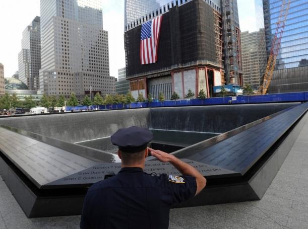 New York City Police Officer Danny Shea salutes at the National September 11 Memorial in New York, September 11, 2011