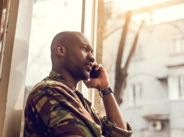 A soldier talking on a cell phone