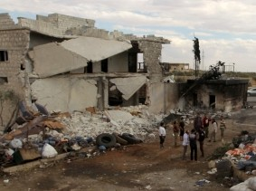 People stand near damaged aid supplies after an airstrike on September 20 on the rebel held Urem al-Kubra town, western Aleppo city, Syria, September 23, 2016