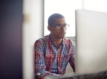 A young man looking at a computer screen