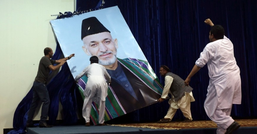 Supporters of Afghan presidential candidate Abdullah Abdullah take down a large portrait of Afghan President Hamid Karzai before a gathering in Kabul July 8, 2014