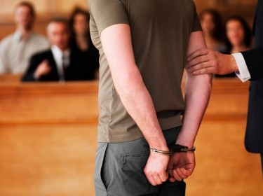 Handcuffed man standing in a courtroom