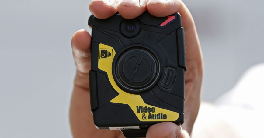 Police Constable Yasa Amerat poses for a photograph with a body-worn video (BWV) camera, before a year-long trial by the Metropolitan police, at Kentish Town in London, May 6, 2014.