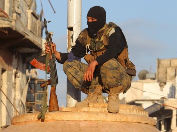 A member of the Nusra Front squats in Ariha, Syria, after a coalition of insurgent groups seized the area, May 29, 2015
