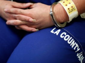 A woman sits handcuffed after arriving at the Los Angeles Century Jail for Women in Lynwood, California, April 26, 2013