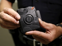 A Los Angeles Police Department officer displays new body cameras in Los Angeles, California, August 31, 2015