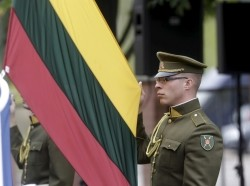 A Lithuanian army soldier holds the national flag during the NATO Force Integration Unit inauguration event in Vilnius, Lithuania, September 3, 2015