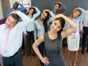 Coworkers taking a break in the office to stretch
