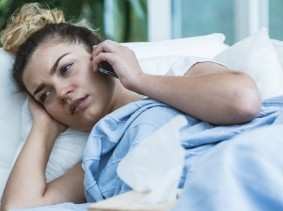A woman sick in bed calling her doctor