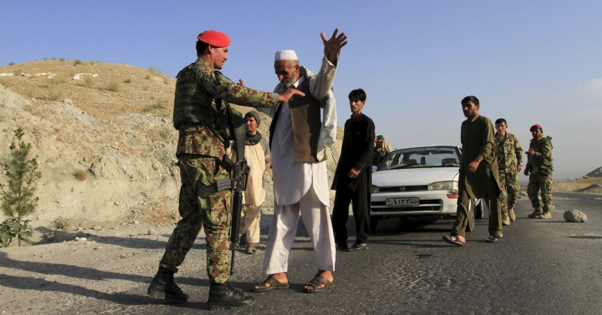 Afghan National Army soldiers inspect passengers at a checkpoint in eastern Afghanistan, June 29, 2015, after Islamic State fighters had seized territory from rival Taliban insurgents in Afghanistan for the first time