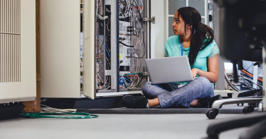 Female IT professional checking on network servers using a laptop